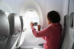 Young woman in plane taking photo Royalty Free Stock Photos