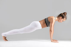Young woman in Plank pose, grey studio background Stock Image