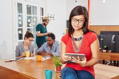 Young woman planning with tablet. Young women planning project with tablet in startup coworking office Stock Photography