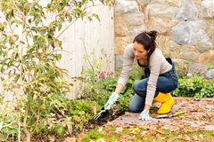 Young woman planting backyard flowerbed autumn Stock Photos