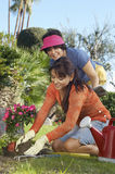 Young Woman Planting flower With Mother Standing Behind Stock Image