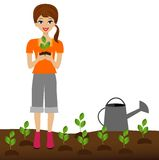 A young woman plants a nursery transplant in soil Stock Photo
