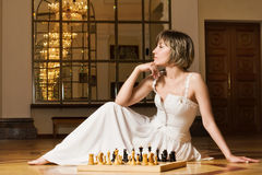 Young Woman Play Chess In The Rich Interior Royalty Free Stock Images