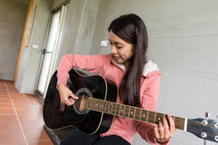 Young Woman play with guitar Stock Image