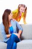 Young woman play with her daughter on sofa Stock Photography