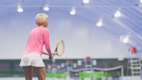 Young woman play tennis. Young beautiful woman is playing tennis at the indoors court. The woman professionally hits the tennis balls and enjoys the game. Pretty stock video footage