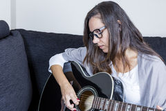 Young woman playing an acoustic guitar Stock Images