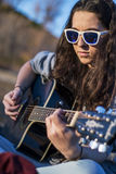 Young woman playing acoustic guitar at dusk Stock Image