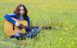 Young woman playing an acoustic guitar in the fields Royalty Free Stock Images