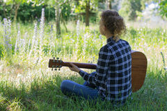 Young woman playing an acoustic guitar in a meadow Stock Images