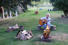Young woman playing acoustic guitar while sitting near campfire royalty free stock images