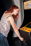 Young woman playing arcade. Woman playing on the machines in the amusement arcade Stock Photos