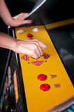 Young woman playing arcade. Woman playing on the machines in the amusement arcade Royalty Free Stock Photo