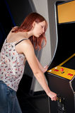 Young woman playing arcade. Woman playing on the machines in the amusement arcade Royalty Free Stock Photos