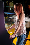 Young woman playing arcade. Woman playing on the machines in the amusement arcade Stock Photography