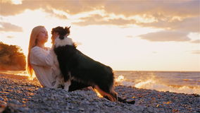 Young woman playing with Australian Shepherd on the shores of a lake or the sea. stock video