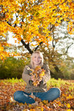 Young woman playing with autumn leaves. Beautiful young blond woman playing with autumn leaves royalty free stock photography