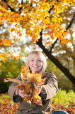 Young woman playing with autumn leaves. Beautiful young blond woman playing with autumn leaves stock photography