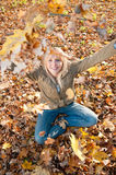 Young woman playing with autumn leaves. Beautiful young blond woman playing with autumn leaves royalty free stock photos