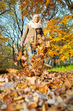 Young woman playing with autumn leaves. Beautiful young blond woman playing with autumn leaves stock image