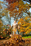 Young woman playing with autumn leaves. Beautiful young blond woman playing with autumn leaves royalty free stock image