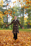 Young woman playing with autumn leaves Stock Photos