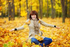 Young woman playing with autumn leaves Royalty Free Stock Images
