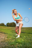 Young woman playing badminton in a city park Stock Photos