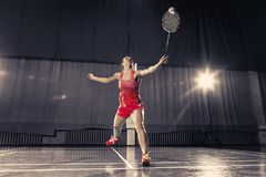 Young woman playing badminton at gym. Young woman playing badminton over gym background Stock Images