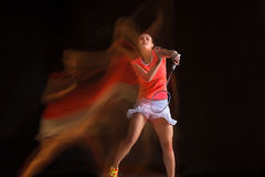 Young woman playing badminton over black background Stock Photo