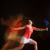 Young woman playing badminton over black background Royalty Free Stock Photo
