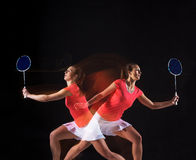 Young woman playing badminton over black background Stock Photography