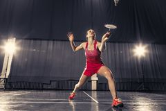 Young woman playing badminton at gym. Young woman playing badminton over gym background Royalty Free Stock Photos