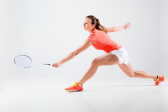 Young woman playing badminton over white background. Young woman playing badminton over white studio background Royalty Free Stock Photos