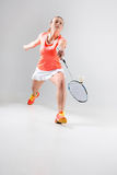 Young woman playing badminton over white background. Young woman playing badminton over white studio background Stock Photography