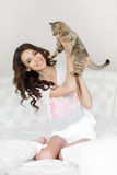 Young woman playing on the bed with the cat Stock Photo