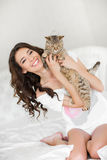 Young woman playing on the bed with the cat Stock Images