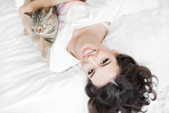 Young woman playing on the bed with the cat Royalty Free Stock Images