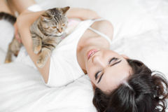 Young woman playing on the bed with the cat Stock Photos