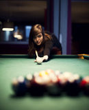Young woman playing billiard Stock Image