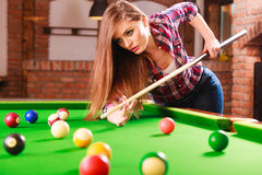 Young woman playing billiard. Royalty Free Stock Image
