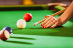 Young woman playing billiard. Competition concept. Young woman having fun with billiard. Female hand holding cue stick playing Royalty Free Stock Images