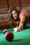 Young Woman Playing Billiards. Young Woman Concentrating While Playing Pool. Vertical shot stock image