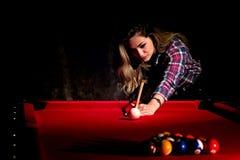 Young woman playing billiards in the dark billiard club.  stock image
