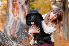 Young woman playing with black puppy in the autumn forest Royalty Free Stock Photography