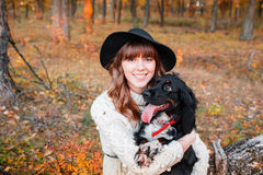 Young woman playing with black puppy in the autumn forest Royalty Free Stock Images