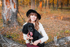 Young woman playing with black puppy in the autumn forest Royalty Free Stock Photo