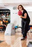 Young Woman Playing in Bowling Alley At Club Royalty Free Stock Photos