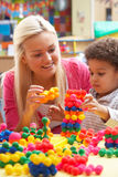 Young woman playing with boy. And toys Royalty Free Stock Photography
