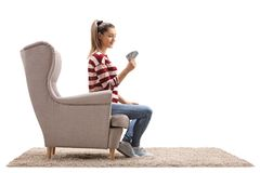 Young woman with playing cards sitting in an armchair Stock Photos